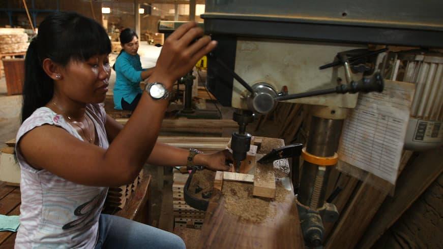 Female worker operating a pillar drill. Japera, Central Java, Indonesia.