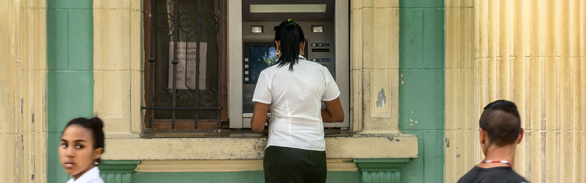Woman using ATM in Cuba
