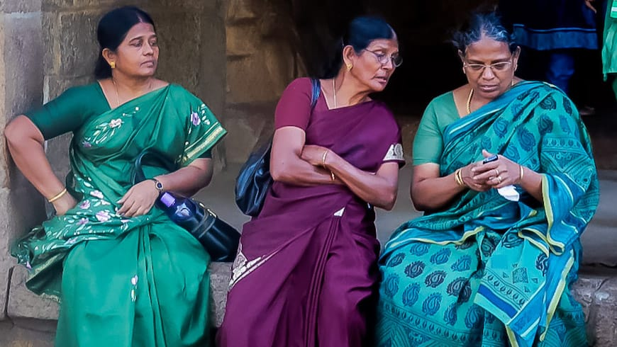 Three Indian women in beautiful saris sit together and one tries to see what another is doing on her cell phone