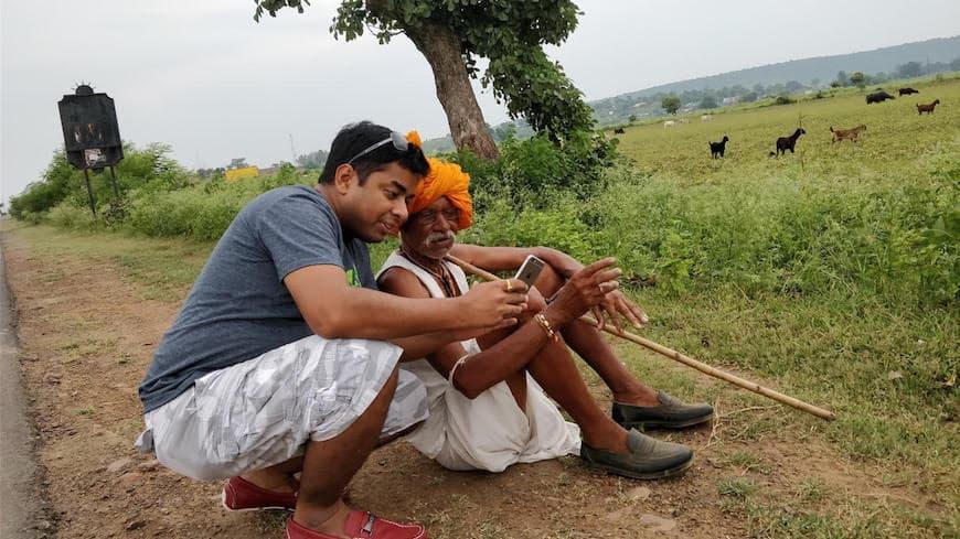 Ruchit G Garg of Harvesting is advising a farmer using his smartphone.