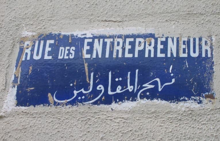 "Image: A sign in French and Arabic reads ""entrepreneur street."""