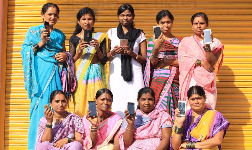 Women workers with Haqdarshak hold up their smartphones.