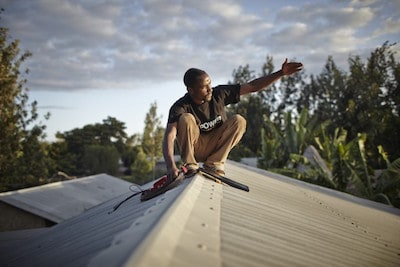 An M-POWER agent installs a solar panel in Tanzania. (Image credit: Mathieu Young / Off Grid Electric).