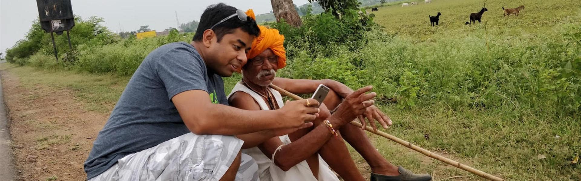 Ruchit G Garg of Harvesting is advising a farmer using his smartphone.