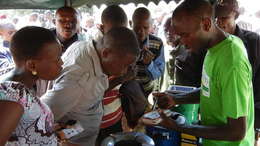A sales representative from Juhudi Kilimo shows farmers various products.