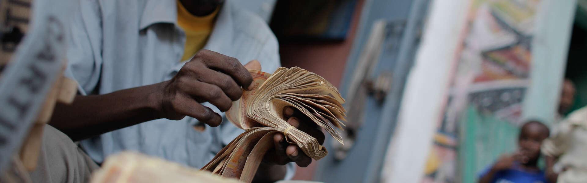 A money exchanger counts Somali shilling notes on the streets of the Somali capital Mogadishu. NextBillion.net