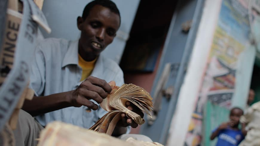A money exchanger counts Somali shilling notes on the streets of the Somali capital Mogadishu. NextBillion.net
