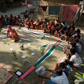 A group of men and women attend a Participatory Rural Appraisal (PRA) in Kaposhatia in Pakchanda union in Hossanipur upazila, Bangladesh.