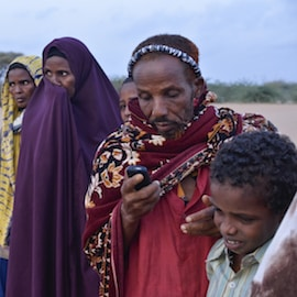Sahal Gure Mohamed texts on his cell phone while waiting in line at dawn to register at Ifo refugee camp in Dadaab, Kenya.